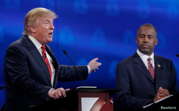 U.S. presidential candidate and businessman Donald Trump, left, speaks as Ben Carson, a retired neurosurgeon, listens at the 2016 U.S. Republican presidential candidates debate held by CNBC in Boulder, Colo., Oct. 28, 2015.