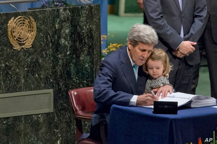 U.S. Secretary of State John Kerry holds his granddaughter as he signs the Paris Agreement on climate change at U.N. headquarters, April 22, 2016.