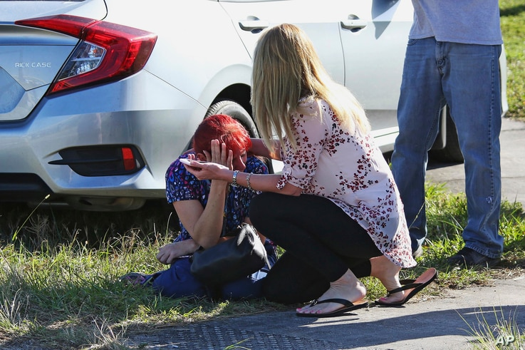 A woman consoles another as parents wait for news regarding a shooting at Marjory Stoneman Douglas High School in Parkland, Fla., Feb. 14, 2018.