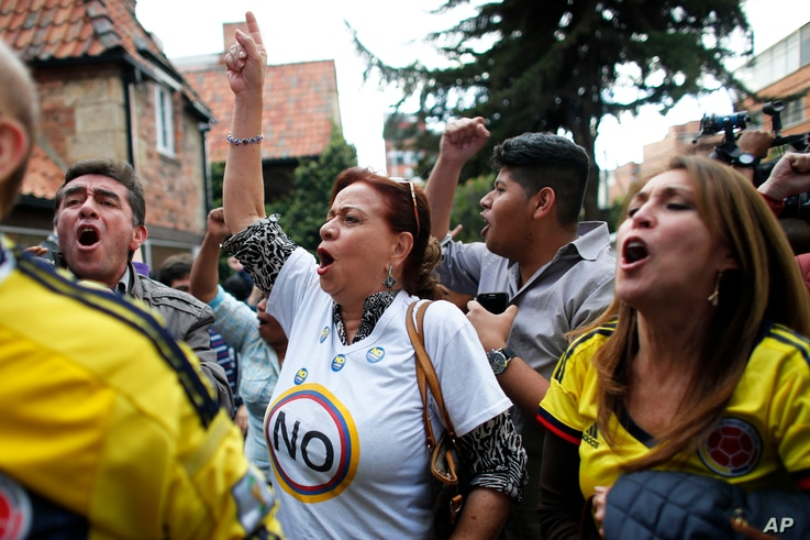 Opponents to the peace deal signed between the Colombian government and rebels of the Revolutionary Armed Forces of Colombia, FARC, celebrate as they listen to the results of the referendum to decide whether or not to support a peace accord to in Bog...
