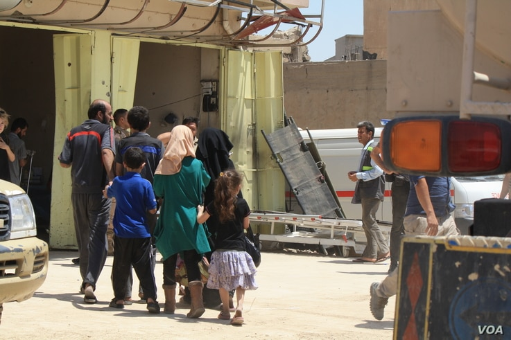 After Raqia was shot in her chest as she ran on June 4, 2017, her children and grandchildren crowd into a field clinic as she is treated in Mosul, Iraq. (H. Murdock/VOA)
