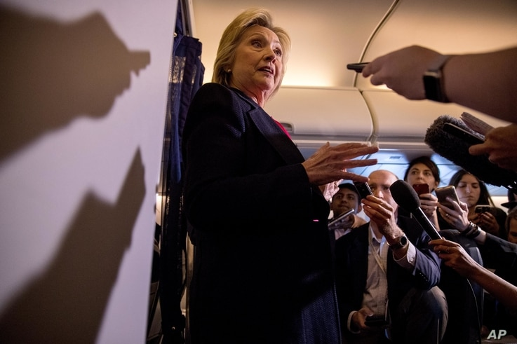Democratic presidential candidate Hillary Clinton speaks to members of the media on board her campaign plane as she travels to Tampa, Sept. 6, 2016.