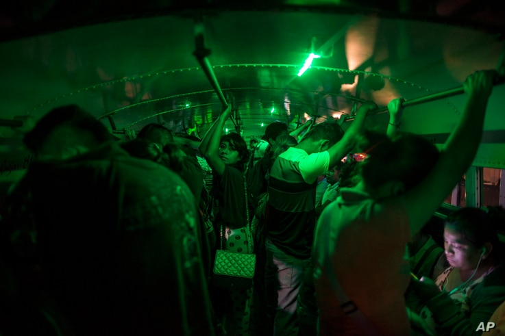 """People stand in a bus as they wait to go home after their work day at a """"maquiladora"""" in Matamoros, Tamaulipas state, Mexico, across the border from Brownsville, Texas, March, 22, 2017."""