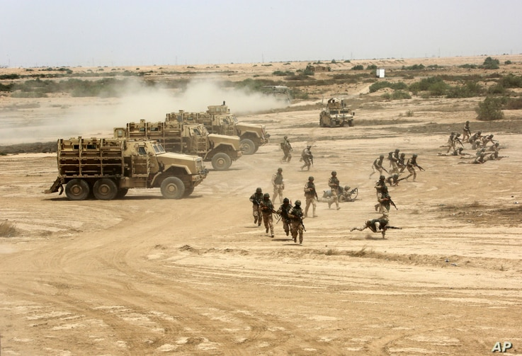 Iraqi, U.S. and Spanish soldiers participate in a training mission outside Baghdad, Iraq, Wednesday, May 27, 2015. Islamic State extremists unleashed a wave of suicide attacks targeting the Iraqi army in western Anbar province, killing at least 17 tr...