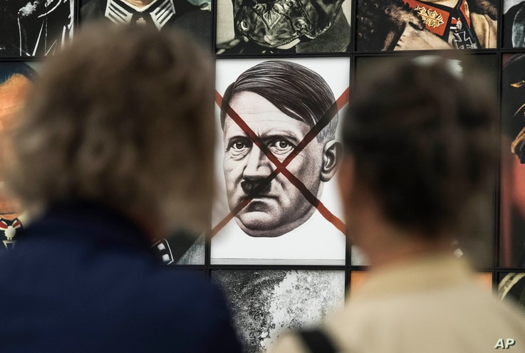 FILE - Visitors stand in front of the work 'Real Nazi' by Polish artist Piotr Uklanski during the press preview of the documenta 14, the world's most significant exhibition of contemporary art, in Kassel, Germany, June 8, 2017.
