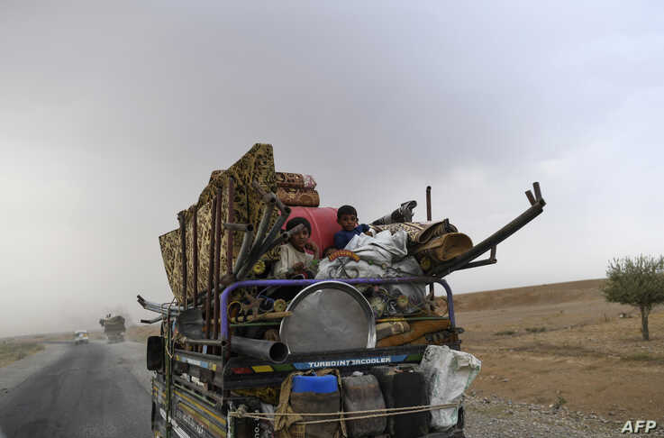 Displaced Syrians from Deir el Zour head to refugee camps on the outskirts of Raqa on Sept. 24, 2017 as Syrian fighters backed by US special forces are battling to clear the last remaining Islamic State group jihadists holed up in their crumbling str