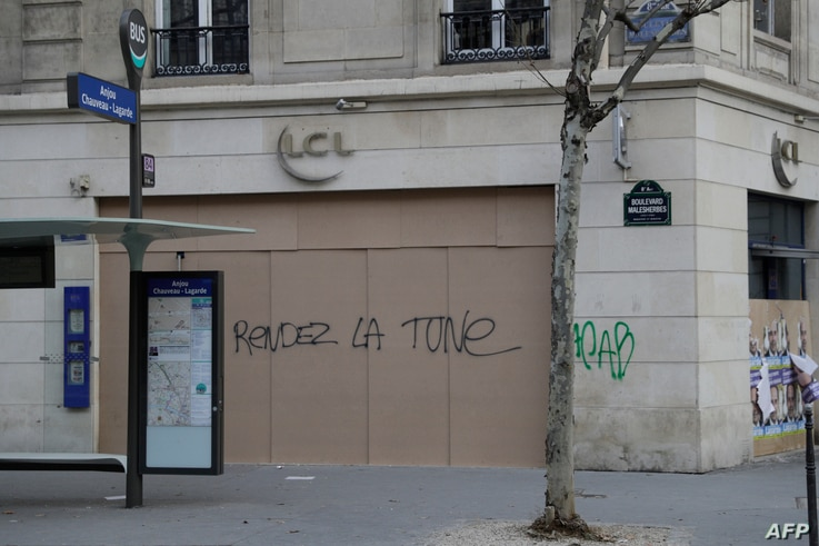 "The words ""Give back the money"" are written on the facade of a bank in Paris, Dec. 15, 2018, as protesters wearing yellow vests arrive to demonstrate against rising costs of living they blame on high taxes."