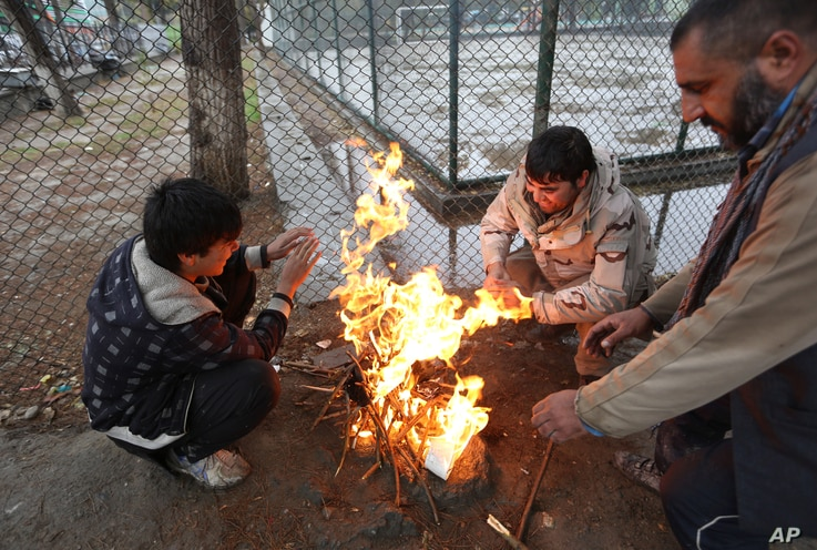 Afghan men warm themselves near a fire in Kabul, Afghanistan, Nov. 10, 2015. Extreme poverty makes difficulties for Afghans to cope with the cold winter.