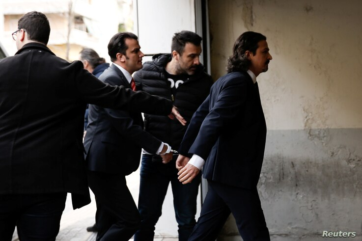 FILE - Two of the eight Turkish soldiers, who fled to Greece in a helicopter and requested political asylum after a failed military coup against the government, are escorted by police officers as they arrive at the appeals court in Athens, Greece, Ma...
