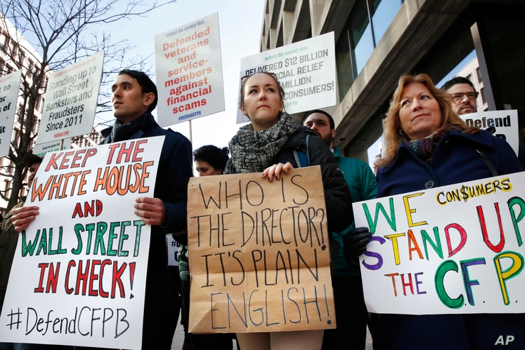 Mike Litt, left, Kaitlyn Vitez, and Ruth Susswein, gather with other members of consumer advocate groups to protest outside of the Consumer Financial Protection Bureau in Washington during a news conference with consumer groups that oppose Mick Mulva...