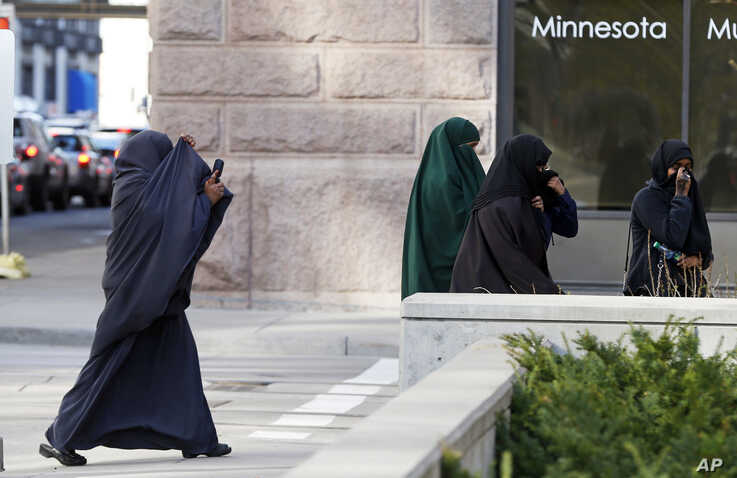 FILE - Female members of Minnesota's Somali community cover their faces as they arrive on April 23, 2015, for a detention hearing in federal court in St. Paul, Minnesota, in the case of several Minnesotans accused of plotting to travel to Syria to jo...