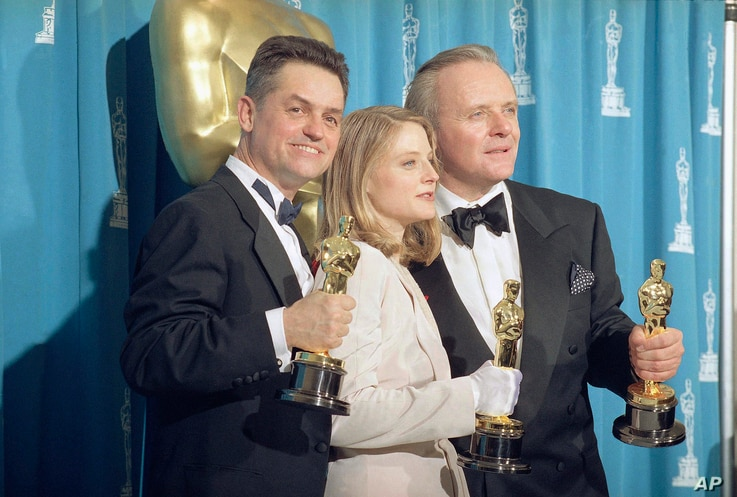 "Director Jonathan Demme, left, stands with actress Jodie Foster and actor Anthony Hopkins,  May 31, 1992, in Los Angeles at the Academy Awards.  All three won top honors for ""Silence of the Lambs,"" which took best picture award."