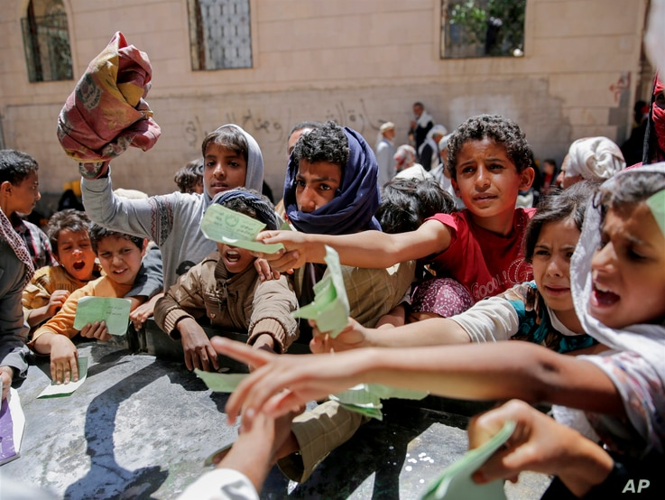 FILE - In this April 13, 2017, photo, Yemenis present documents in order to receive food rations provided by a local charity, in Sanaa, Yemen.