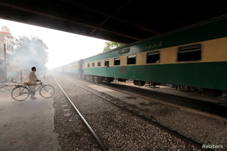 A man waits to cross a portion of track once shared with the Karachi Circular Railway line in Karachi, Pakistan, May 24, 2017.