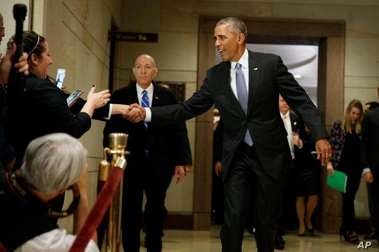 President Barack Obama shakes hands with bystanders as he leaves a meeting about his signature healthcare law with members of Congress, Jan. 4, 2017 on Capitol Hill in Washington.