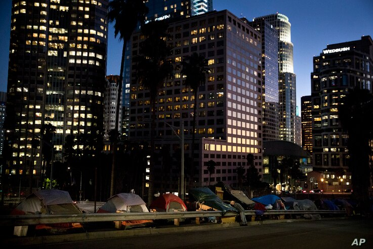 """Homeless tents are dwarfed by skyscrapers as 63-year-old Vincent, who gave only his first name, sorts his belongings, Dec. 1, 2017, in Los Angeles. Vincent said he never had to worry about getting a job as a young man. """"Things ain't the way they wer..."""