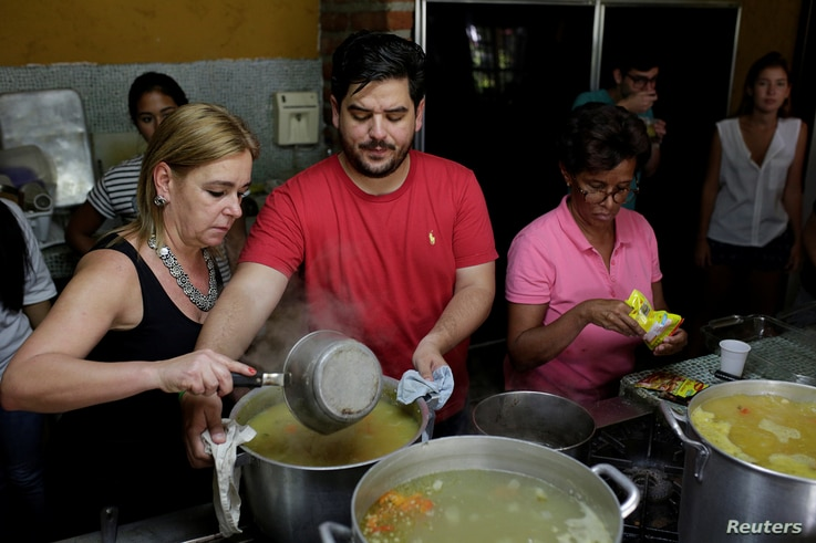 Diego Prada (C), Maria Luisa Pombo (L) and other volunteers of the Make The Difference (Haz La Diferencia) charity initiative prepare soup to be donated, at Maria Luisa's kitchen in Caracas, Venezuela, March12, 2017.