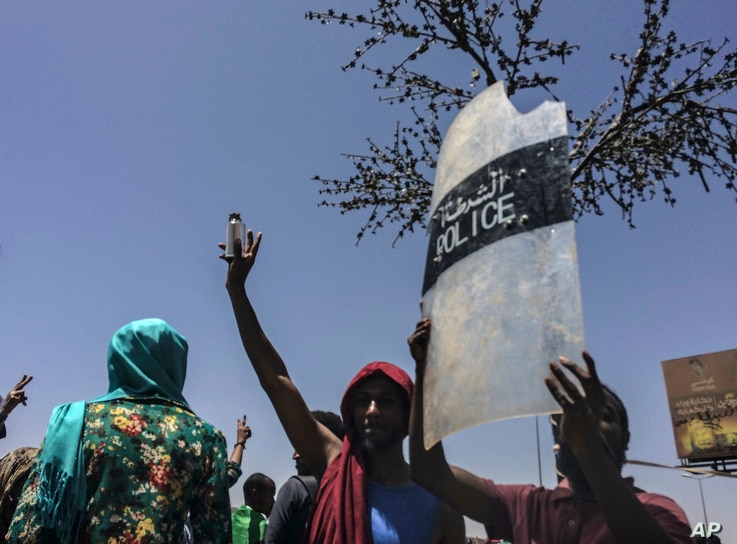 A protester holds up a police shield at a rally in front of the military headquarters in the capital Khartoum, Sudan, Monday, April 8, 2019.