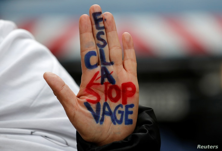"A woman displays her hand with the message ""Stop slavery"" as she attends a protest against slavery in Libya outside the Libyan Embassy in Paris, France, Nov. 24, 2017."