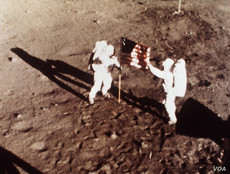 """In this July 20, 1969 file photo, Apollo 11 astronauts Neil Armstrong and Edwin E. """"Buzz"""" Aldrin, the first men to land on the moon, plant the U.S. flag on the lunar surface. Photo was made by a 16mm movie camera inside the lunar module, shooting at ..."""
