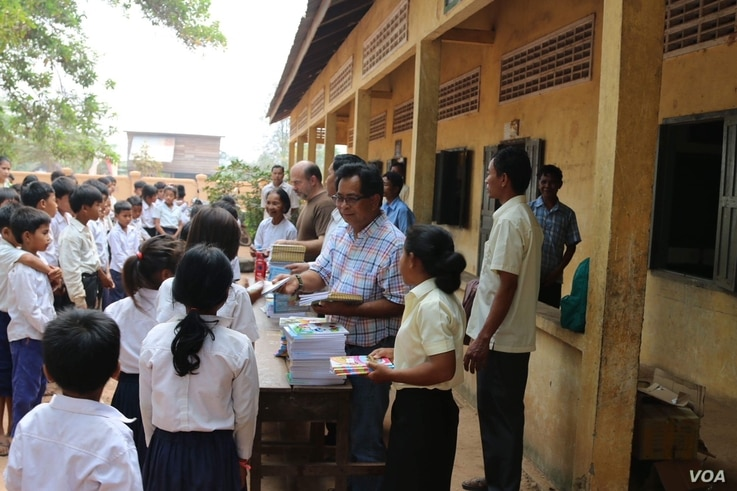 Im Chaem with students during donation of books, pen and study tools with a US Christian missionary team led by Pastor Christopher LaPel in November 2017 near her home in O'Angre village, Anlong Veng District, Oddar Meanchey province. Photo by Pastor...
