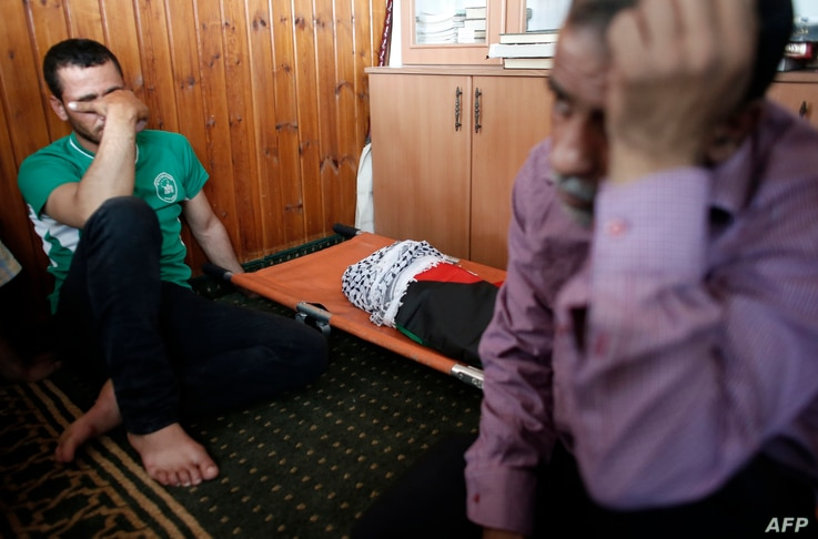 Relatives of 18-month-old Palestinian toddler Ali Saad Dawabsha, who died after his house was set on fire by Jewish settlers, mourn next to his body lying at a mosque during his funeral in the West Bank village of Duma, July 31, 2015.
