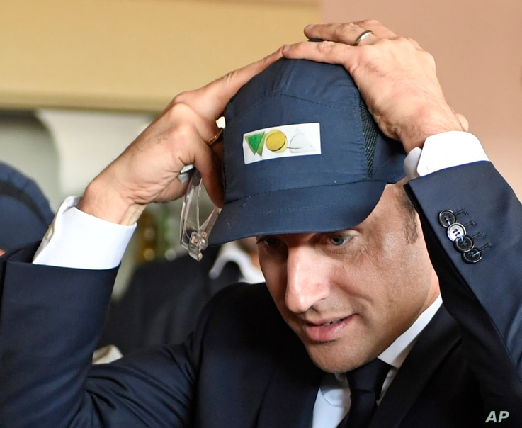 French presidential election candidate for the En Marche ! movement Emmanuel Macron, adjusts his cap during a visit to the VOA glass-making company as part of a a campaign trip in Albi, southwestern France, Thursday, May 4, 2017.