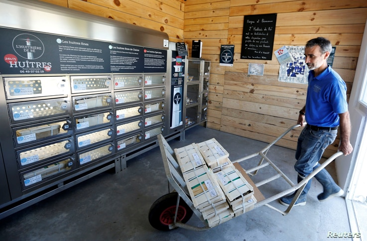 The aquaculturist Tony Berthelot arrives with oysters at l'huitriere de Re, where automatic oyster vending machine is set, in Ars en Re on the Re Island, Southwestern France, Aug. 2, 2017.