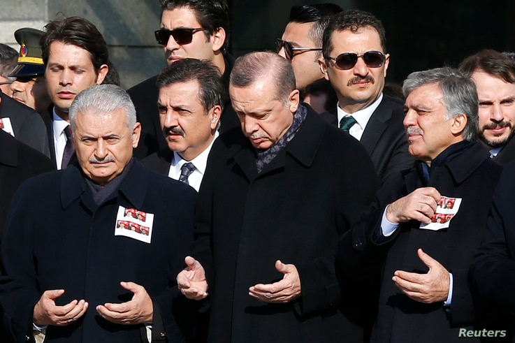 Turkish Prime Minister Binali Yildirim, President Tayyip Erdogan and Former President Abdullah Gul pray during a ceremony for police officers killed in Saturday's blasts in Istanbul, Dec.  11, 2016.