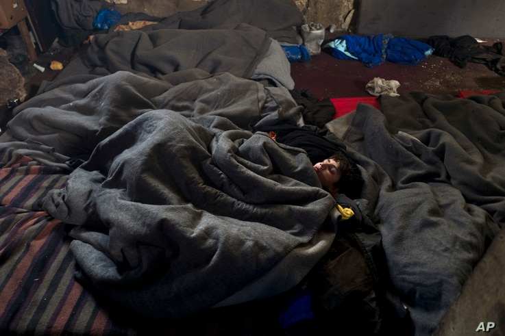 A migrant sleeps on the ground of an abandoned warehouse where he and other migrants took refuge in Belgrade, Serbia, Feb. 11, 2017.