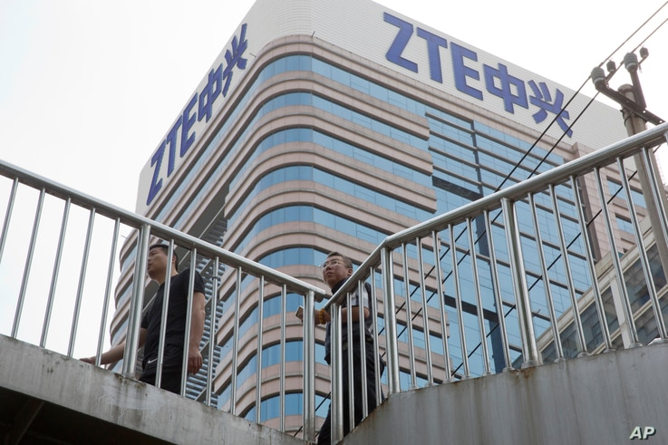 FILE - Men pass by a building of Chinese tech giant ZTE, in Beijing, China, May 8, 2018.