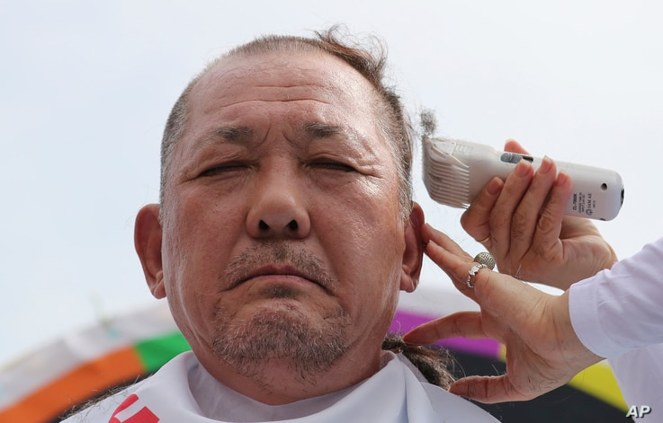 Kim Hang-gon, an administrative chief of Seongju County, has his head shaved during a protest against a plan to deploy an advanced U.S. missile defense system called Terminal High-Altitude Area Defense, or THAAD, in their neighborhood, in Seoul, Sout...