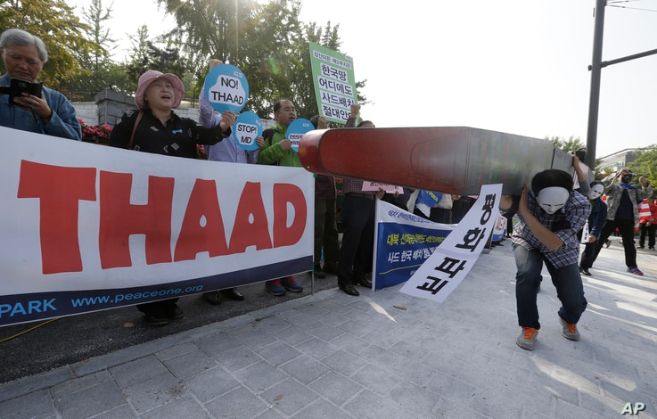 Protesters carry a mock missile symbolizing an advanced U.S. missile defense system called Terminal High-Altitude Area Defense, or THAAD, during a rally to oppose a plan to deploy the THAAD in front of the Defense Ministry in Seoul, South Korea, Oct....