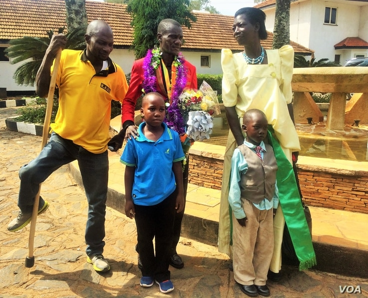 David Emong stands with family members after being received by the Ugandan Paralympic Sports Committee, the Ugandan Sports Council and numerous disabled athletes. (L. Paulat/VOA)