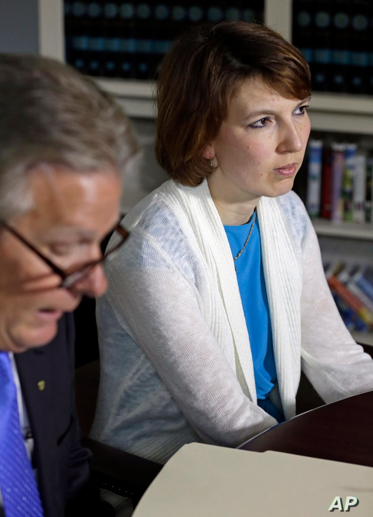 FILE - Tanya Fowle, right, wife of Jeffrey Fowle, listens as attorney Tim Tepe reads a statement from the family in Lebanon, Ohio.