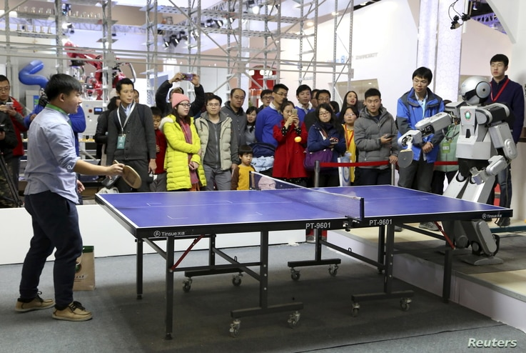 FILE - People look on as a robot (R) plays table tennis with a man during an demonstration at the World Robot Conference in Beijing, China on Nov. 23, 2015.