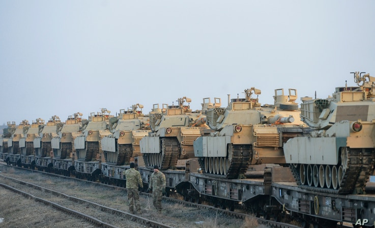 """Servicemen of the """"Fighting Eagles"""" 1st Battalion, 8th Infantry Regiment, walk by tanks that arrived via train to the US base in Mihail Kogalniceanu, eastern Romania, Feb. 14, 2017."""