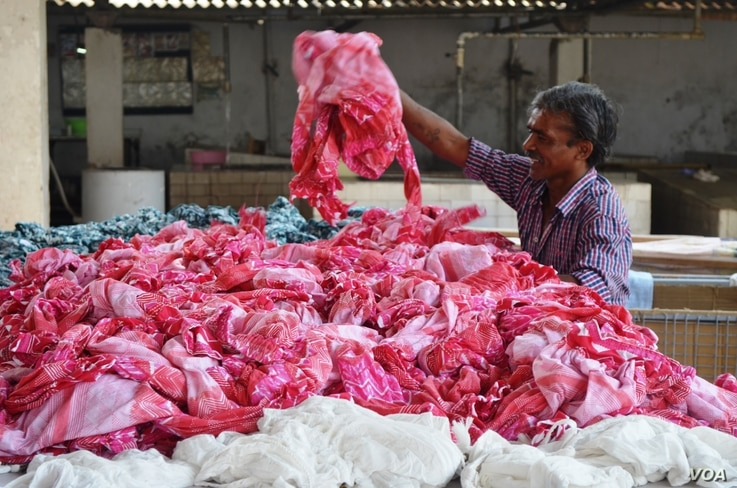 Sorting through garments made for export at an apparel factory in Gurgaon near New Delhi. (A. Pasricha/VOA)