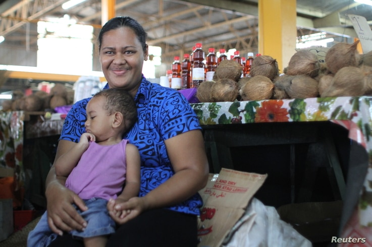 Sofia Talei carries her child in front of her market stall as she poses for a photo for the Thomson Reuters Foundation in Fiji's capital Suva, Dec. 8, 2017.