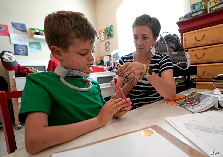 Rachel Scott, right, helps suction the mouth of her son, Braden, in Tomball, Texas, March 29, 2019.