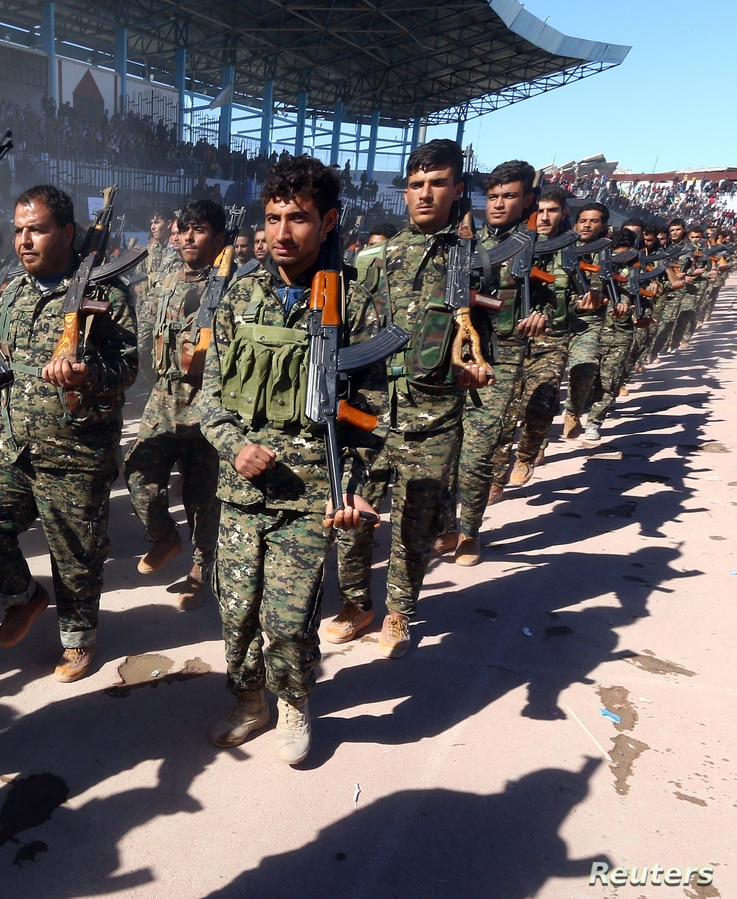 FILE - Troops of the Syrian Democratic Forces celebrate the first anniversary of the liberation of Raqqa province from the Islamic State group, in Raqqa, Syria, Oct. 27, 2018.
