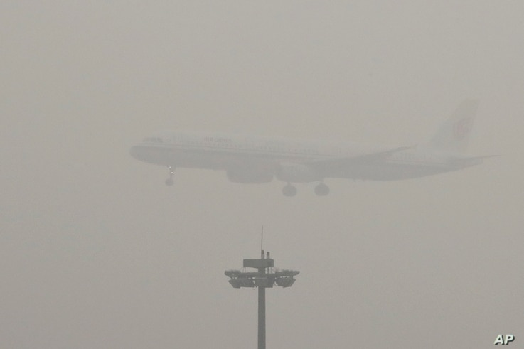 An Air China passenger plane prepares to land at the Beijing Capital International Airport as the capital of China through heavy smog, Dec. 21, 2016.