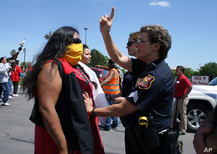 A Rapid City police officer stops a woman during a protest against anti-Native racism in May, 2012.