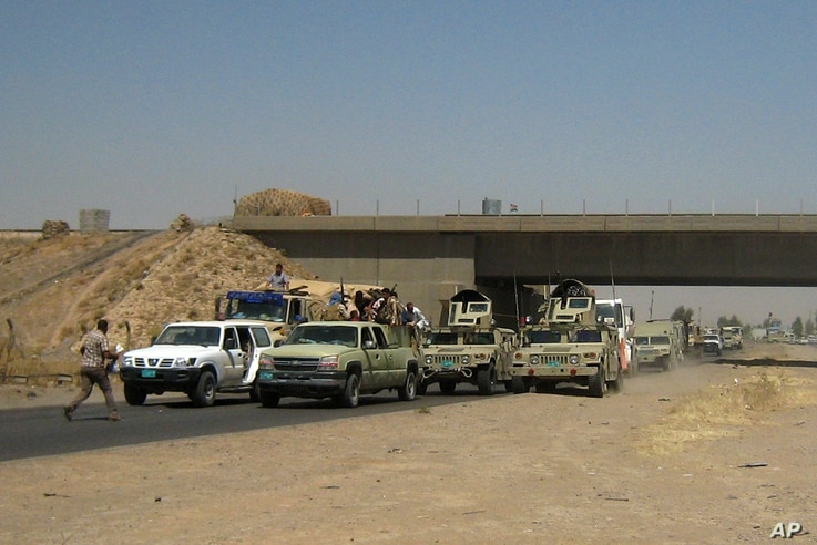 FILE - Iraqi security forces in uniforms and plainclothes head to Baghdad in the main road between Baghdad and Mosul, a day after fighters from the Islamic State of Iraq and the Levant took control of much of Mosul,  June 11, 2014.