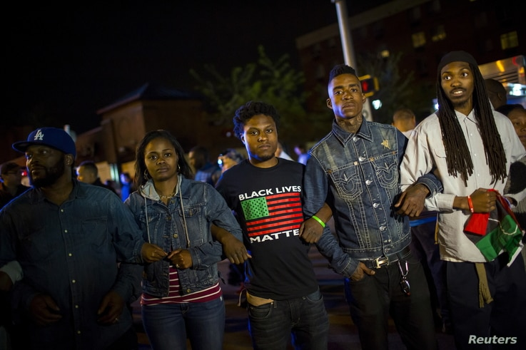 Protestors line up shortly before the deadline for a city-wide curfew at North Ave and Pennsylvania Ave in Baltimore, Maryland, April 30, 2015.