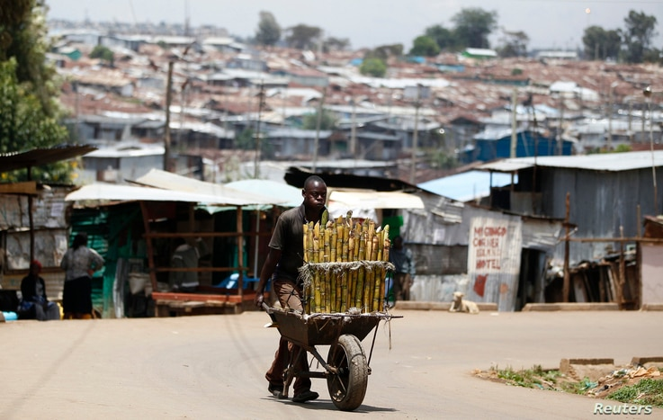 FILE - A vendor sells sugar cane in Kibera slum, home to over 1 million people, in Kenya's capital Nairobi, March 7, 2014.