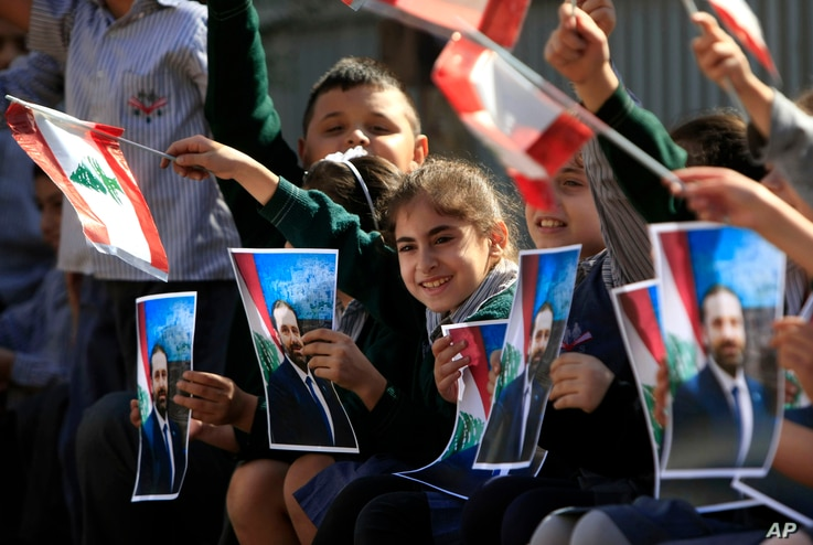 Lebanese students wave portraits of Prime Minister-designate Saad Hariri and Lebanese flags as they celebrate the announcement, in the southern port city of Sidon, Lebanon, Nov. 3, 2016.