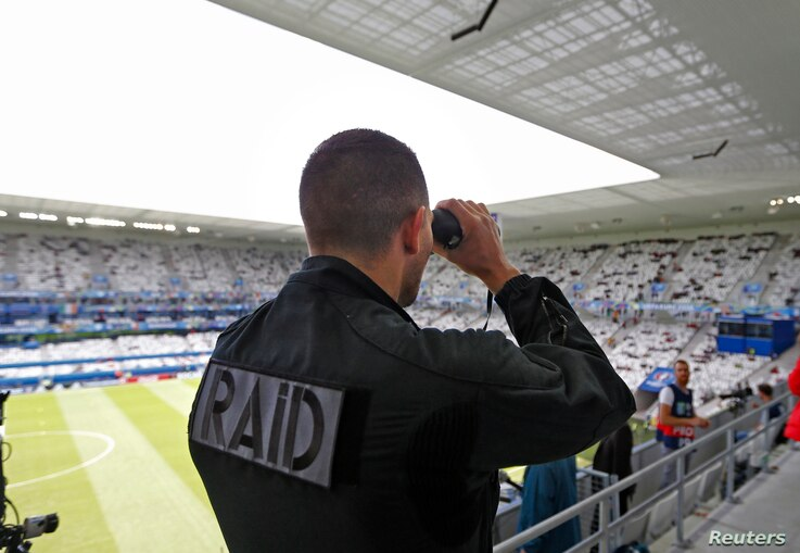 A member of France's rapid intervention police force RAID surveys spectators inside Bordeaux stadium, where Belgium was playing Ireland in Euro 2010 football competition, June 18, 2016.