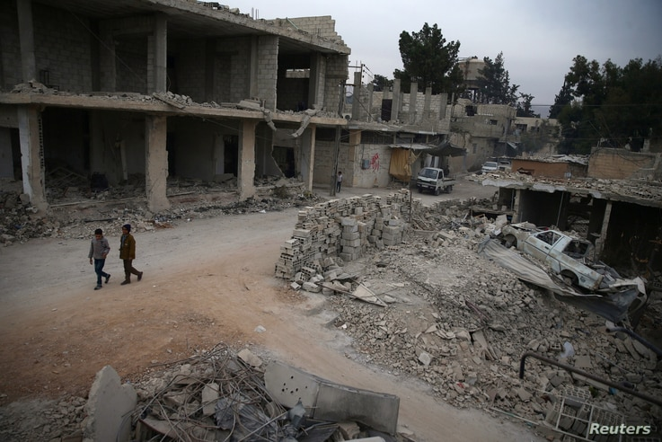 FILE - Children walk near rubble of damaged buildings in the rebel-held besieged city of Douma, in the eastern Damascus suburb of Ghouta, Syria, Nov. 13, 2016.