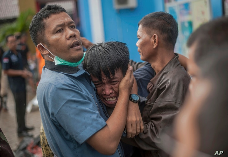 A man reacts after identifying his relative among the bodies of tsunami victims in Carita, Indonesia, Sunday, Dec. 23, 2018.